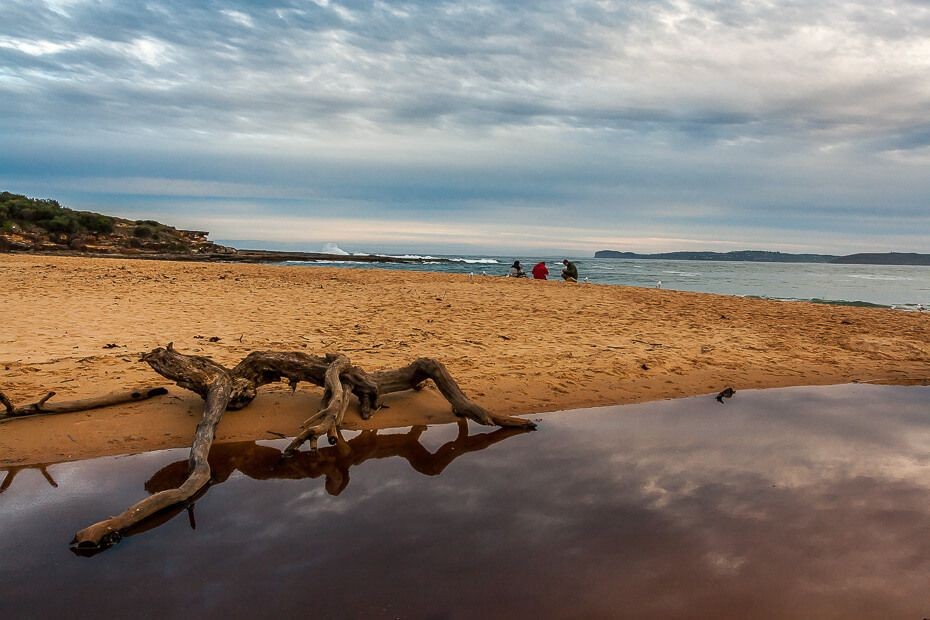 people sitting at Putty Beach at the end of the day