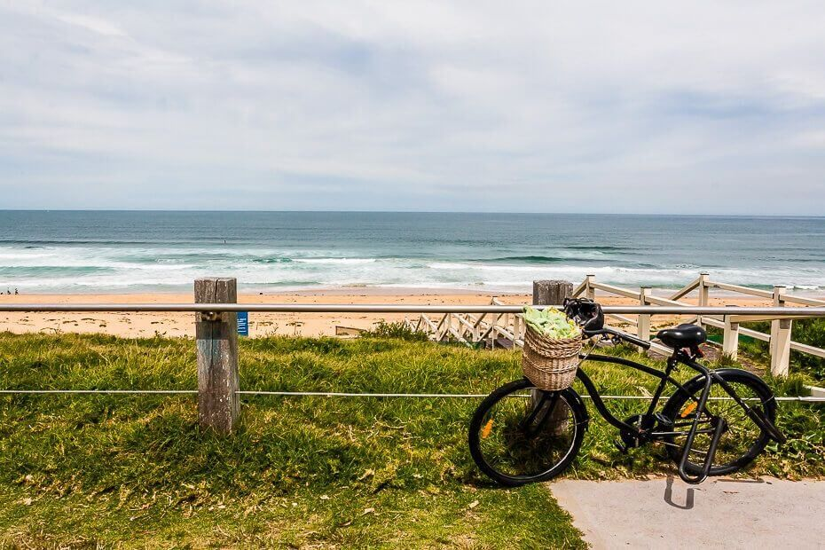 View of the beach, bicycle in the foreground.