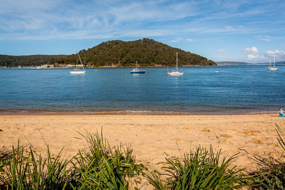 view of beach, boats moored in the water and hill.