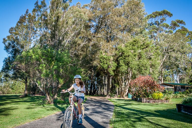 Tuggerah Lake cycle track. Girl cycling along.